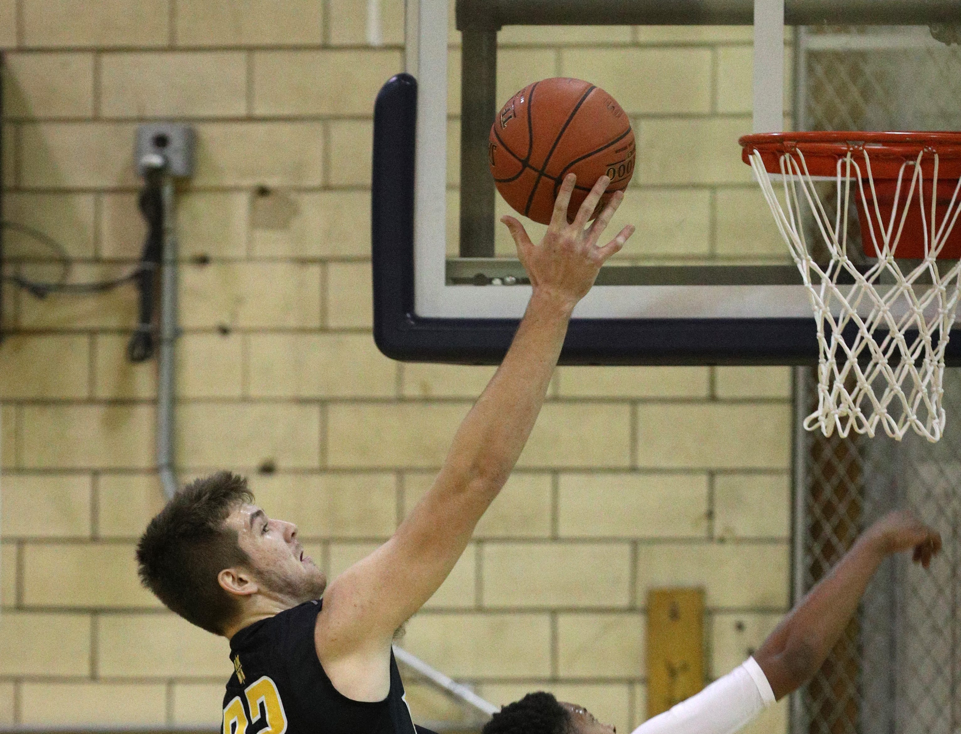 McQuaid's Connor Zamiara (32) drives to the basket against LEadership's Nate Doyle.