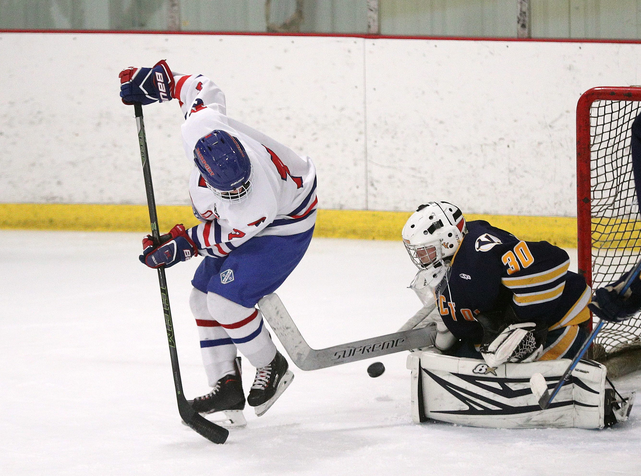 Fairport's Nick Jasie tires to screen Victor goalie Pieter Bartelse.