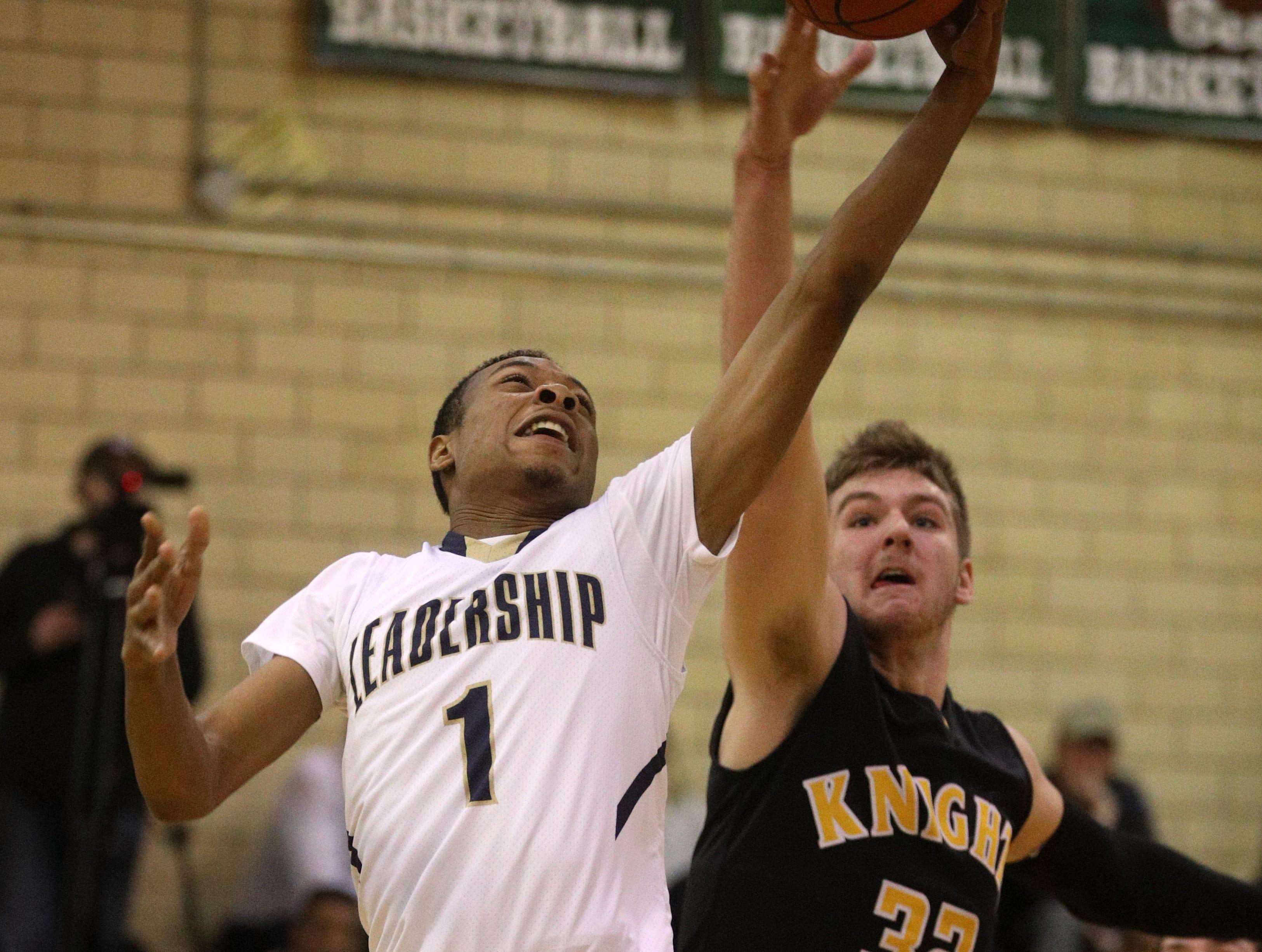 Leadership's Onajae Anderson (1) drives to the basket around McQuaid's  Connor Zamiara.
