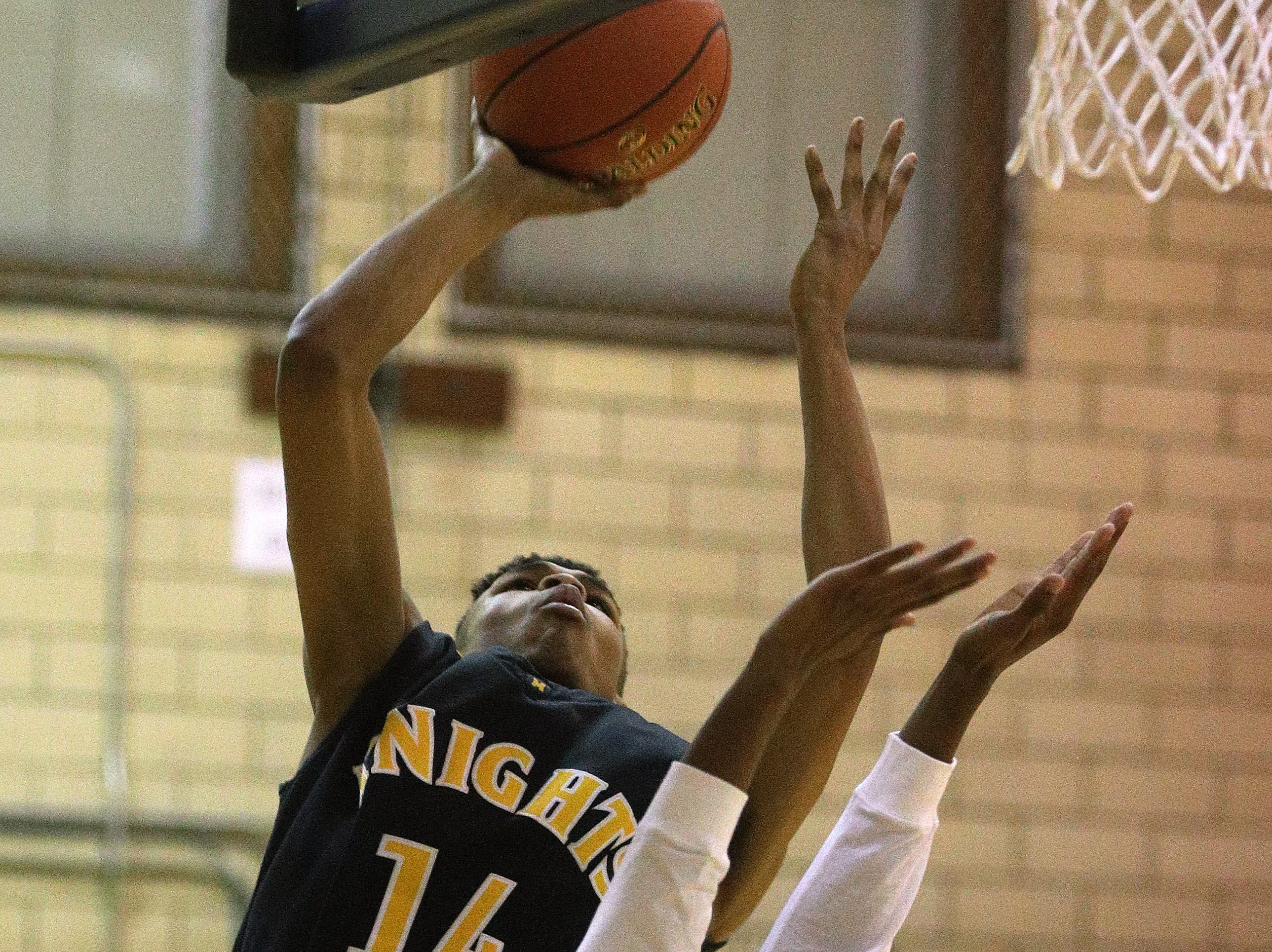 McQuaid's Jermaine Taggart (14) goes up for a shot from under the basket against Leadership's Kennyh Hardeman.