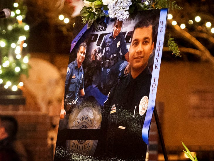 This Friday, Dec. 28, 2018, file photo shows a collection of pictures of police Cpl. Ronil Singh during a candlelight vigil in Newman, Calif. The Northern California police officer was gunned down during a traffic stop the day after Christmas 2018.