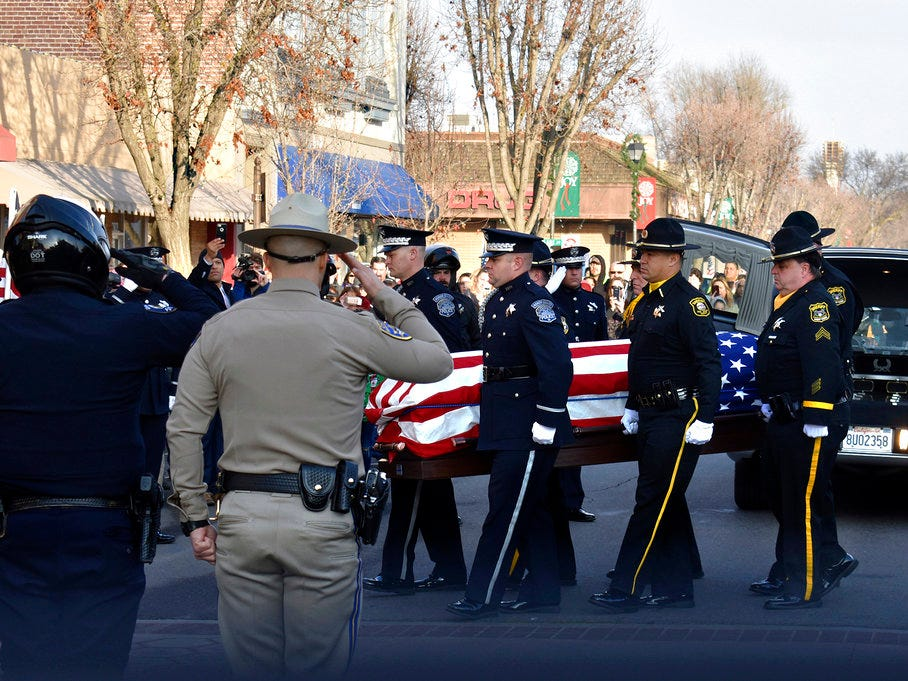 Law enforcement officials carry the casket of Newman police Cpl. Ronil Singh into the Westside Theatre for a public viewing in Newman, Calif., Friday, Jan. 4, 2019. Prosecutors on Wednesday, Jan. 2, charged Gustavo Perez Arriaga in Singh's killing. Perez Arriaga, who was in the country illegally, was arrested after a dayslong manhunt as he prepared to flee to Mexico, authorities said.