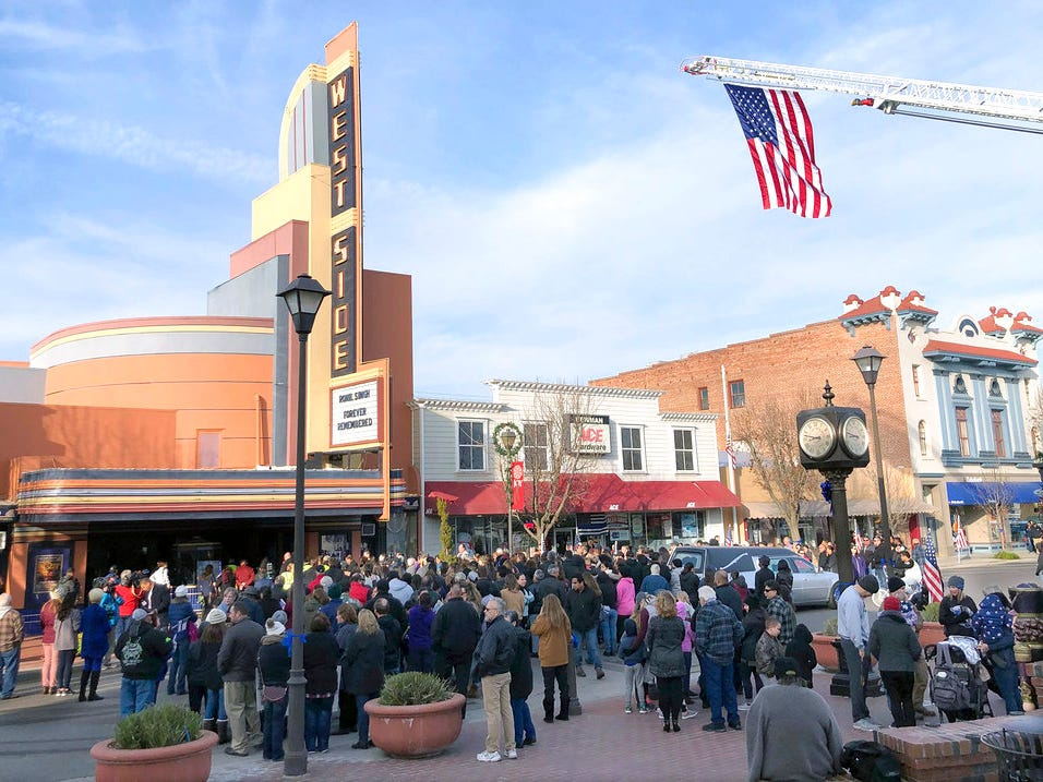 People gather outside the West Side Theatre for the public viewing of Newman police Cpl. Ronil Singh, on Friday, Jan. 4, 2019,  in Newman, Calif. Prosecutors on Wednesday, Jan. 2, charged Gustavo Perez Arriaga in Singh's killing. Perez Arriaga, who was in the country illegally, was arrested after a dayslong manhunt as he prepared to flee to Mexico, authorities said.