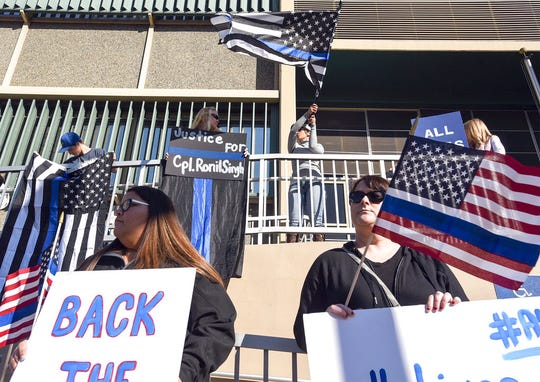People hold flags and signs Wednesday, Jan. 2, 2019, outside the Stanislaus County Superior courthouse in Modesto, Calif., where formal charges were filed against Gustavo Perez Arriaga in the Dec. 26, 2018, shooting death of Newman Police Cpl. Ronil Singh.