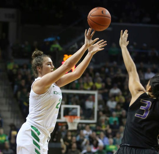 Oregon's Erin Boley, left, shots a three-point basket over Washington's May-Loni Henson during the second quarter of an NCAA college basketball game Friday, Jan. 4, 2019, in Eugene, Ore. (AP photo/Chris Pietsch)