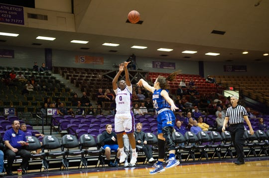 Northwestern State's Nautic Grant shoots over Maddisen Martin during Saturday's game.