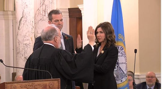 Kristi Noem takes the oath of office during inauguration ceremonies Saturday in Pierre.