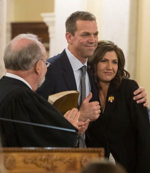 Gov. Kristi Noem is hugged by her husband, Bryon Noem, at her inauguration ceremony in Pierre, S.D., Saturday, Jan. 5, 2019. Noem is the first woman to hold the position of governor in South Dakota.