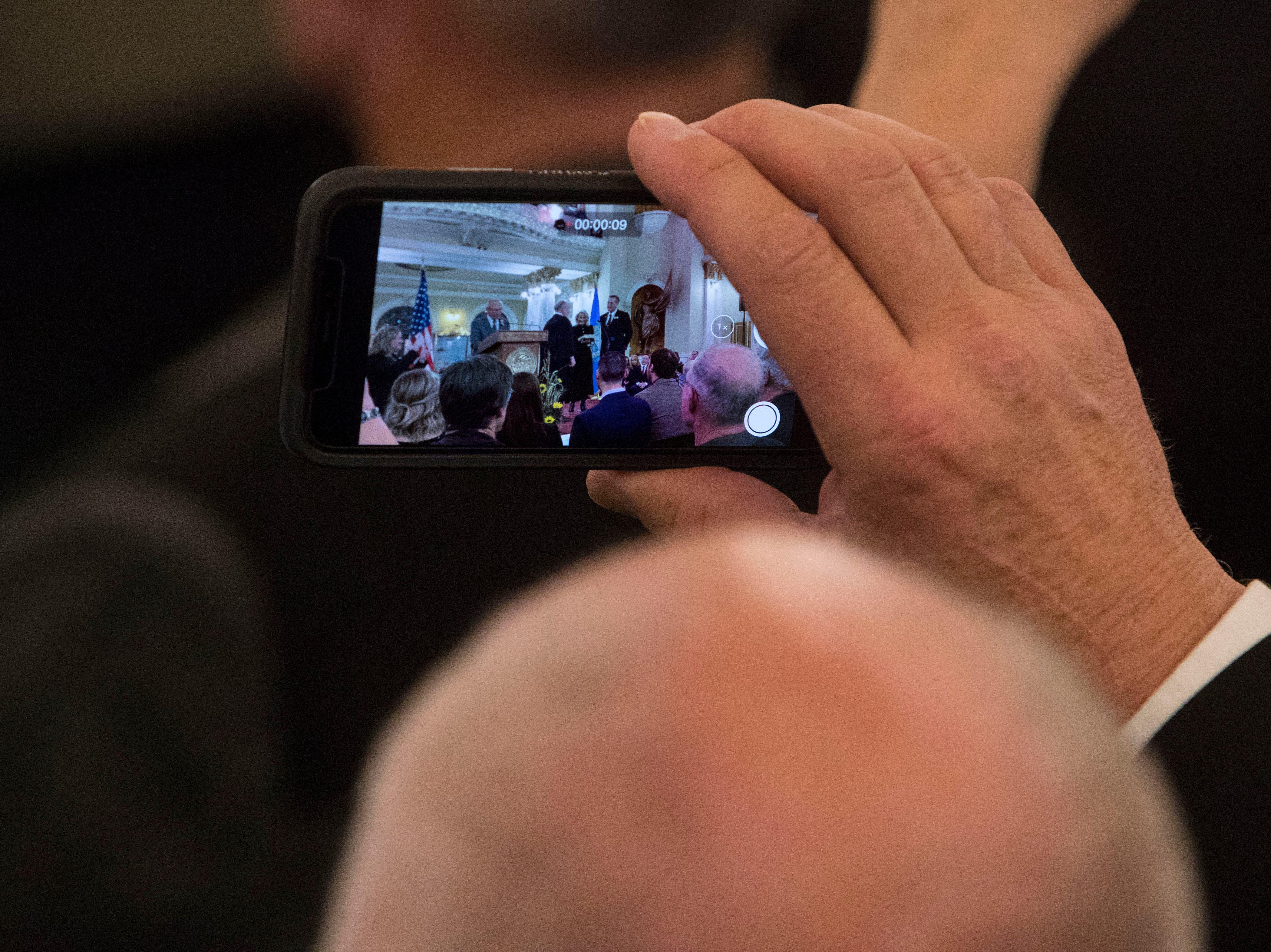 Audience member records Lt. Gov.-elect Larry Rhoden's swearing in ceremony, Saturday, Jan. 5, 2019 in Pierre, S.D.