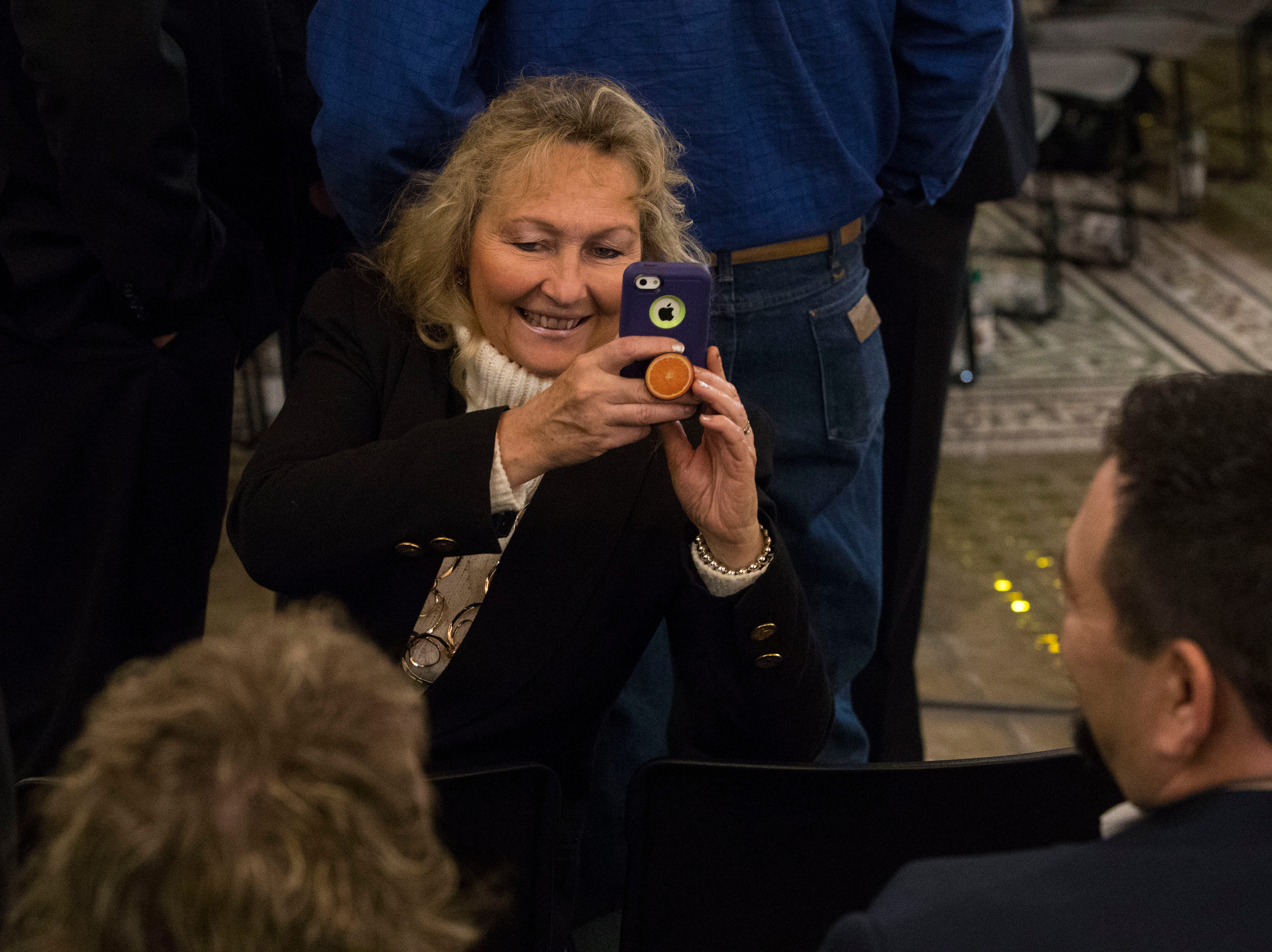 Audience member takes a picture before the inauguration ceremony in Pierre, S.D., Saturday, Jan. 5, 2019.