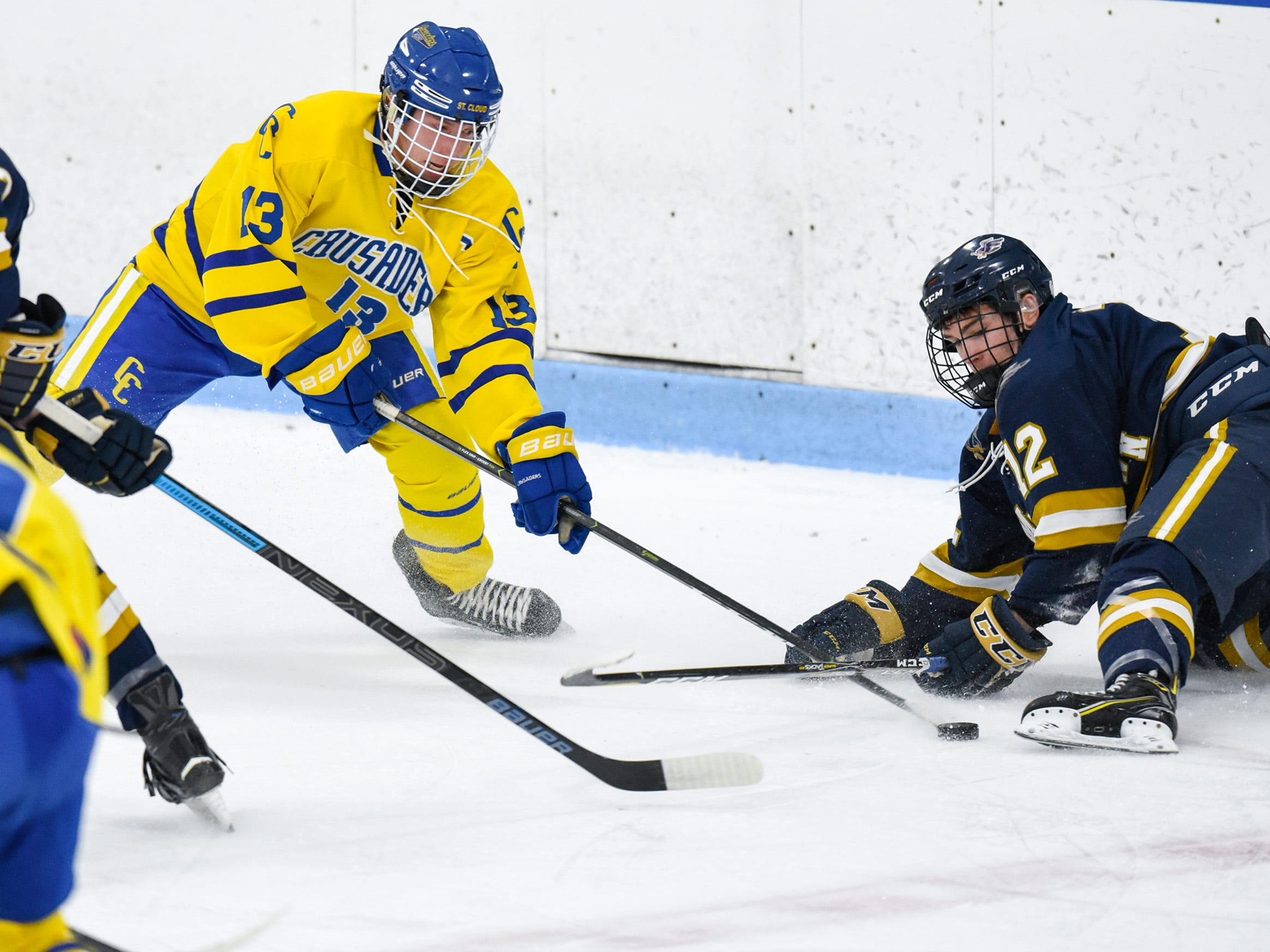 St. Cloud Cathedral's Talon Lenzen moves the puck past Hermantown's Ryan Dobbs during the first period Friday, Jan. 4, at the MAC in St. Cloud.