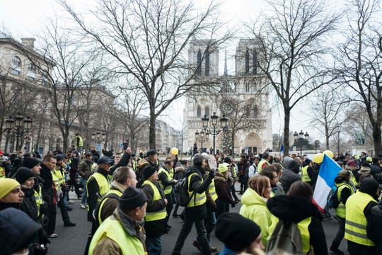 Demonstrators wearing yellow vests march during a protest in Paris, Saturday, Jan. 5, 2019. Hundreds of protesters were trying to breathe new life into France's apparently waning yellow vest movement with marches in Paris and gatherings in other cities. Notre Dame cathedral in the background. (AP Photo/Kamil Zihnioglu)
