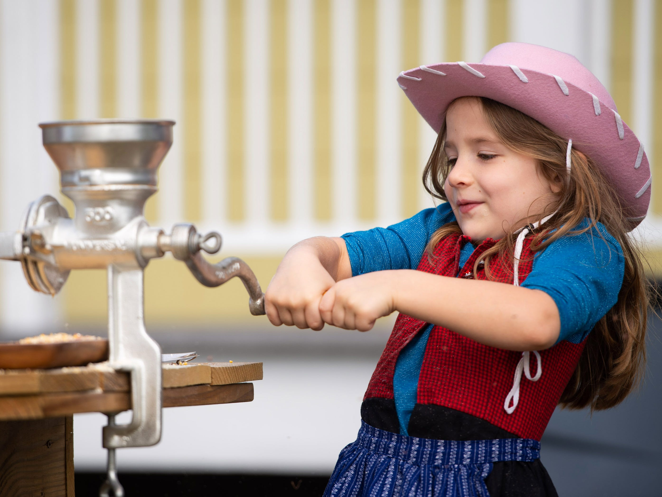 """Becca Kerns, 5, of Port St. Lucie, uses a corn grinder to make cornmeal during the Miss Lucie's 10th annual Pioneer Day Festival at Savannas Preserve State Park on Saturday, Jan. 5, 2019, in Port St. Lucie. """"I like grinding the corn but it is hard work,"""" said Kerns. The festival featured exhibits and demonstrations showcasing how Floridians lived in the mid-19th century."""