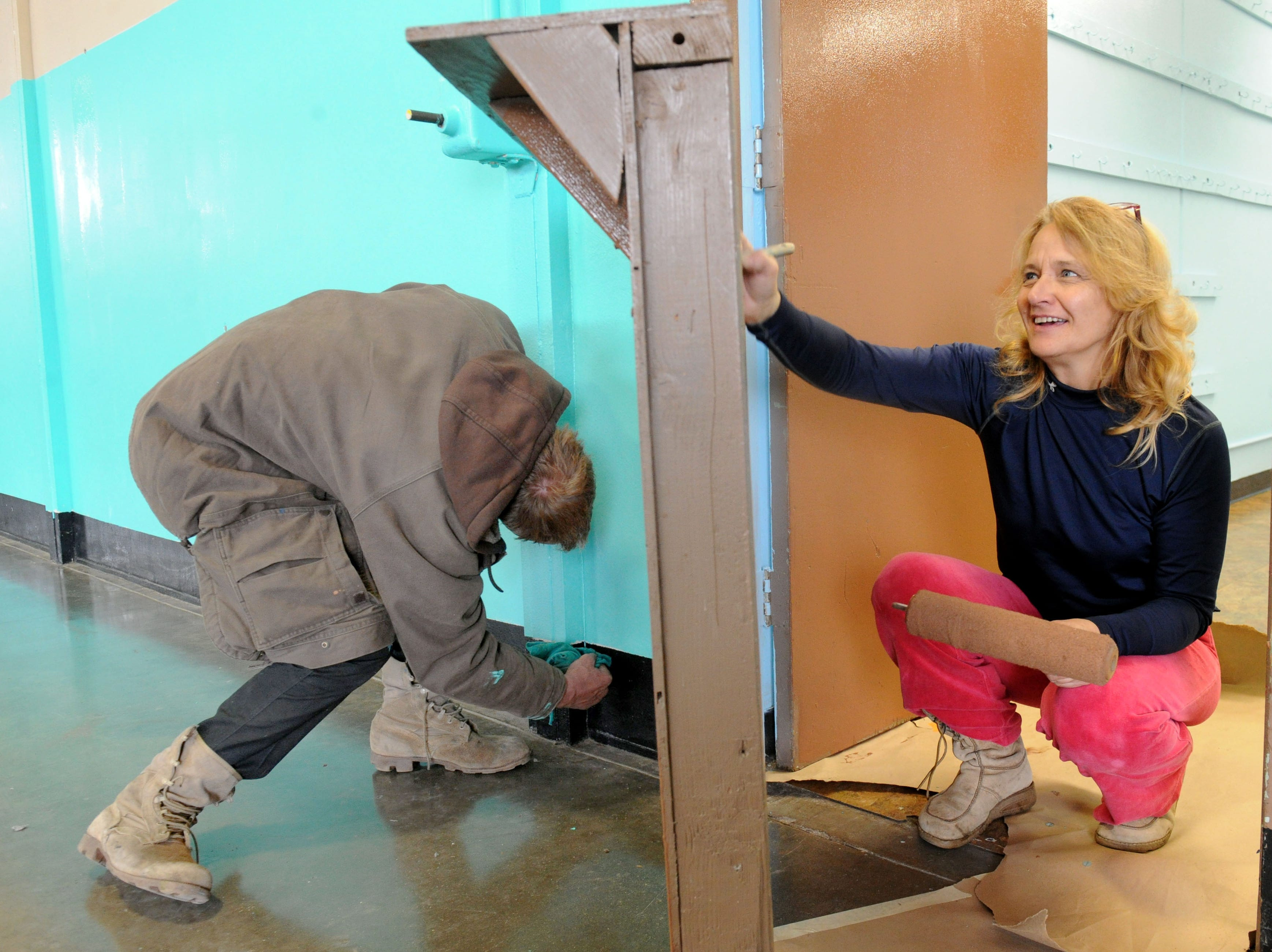Aron Varney (left) and Terrin Howell, of Ojai, help paint the Oxnard National Guard Armory, which will be used as a homeless shelter. Varney is homeless and volunteered to help with the painting and the cleanup efforts. The planned 24-hour shelter on K Street is expected to open this month when staff has been hired but it opened temporarily Saturday night because of  rain.