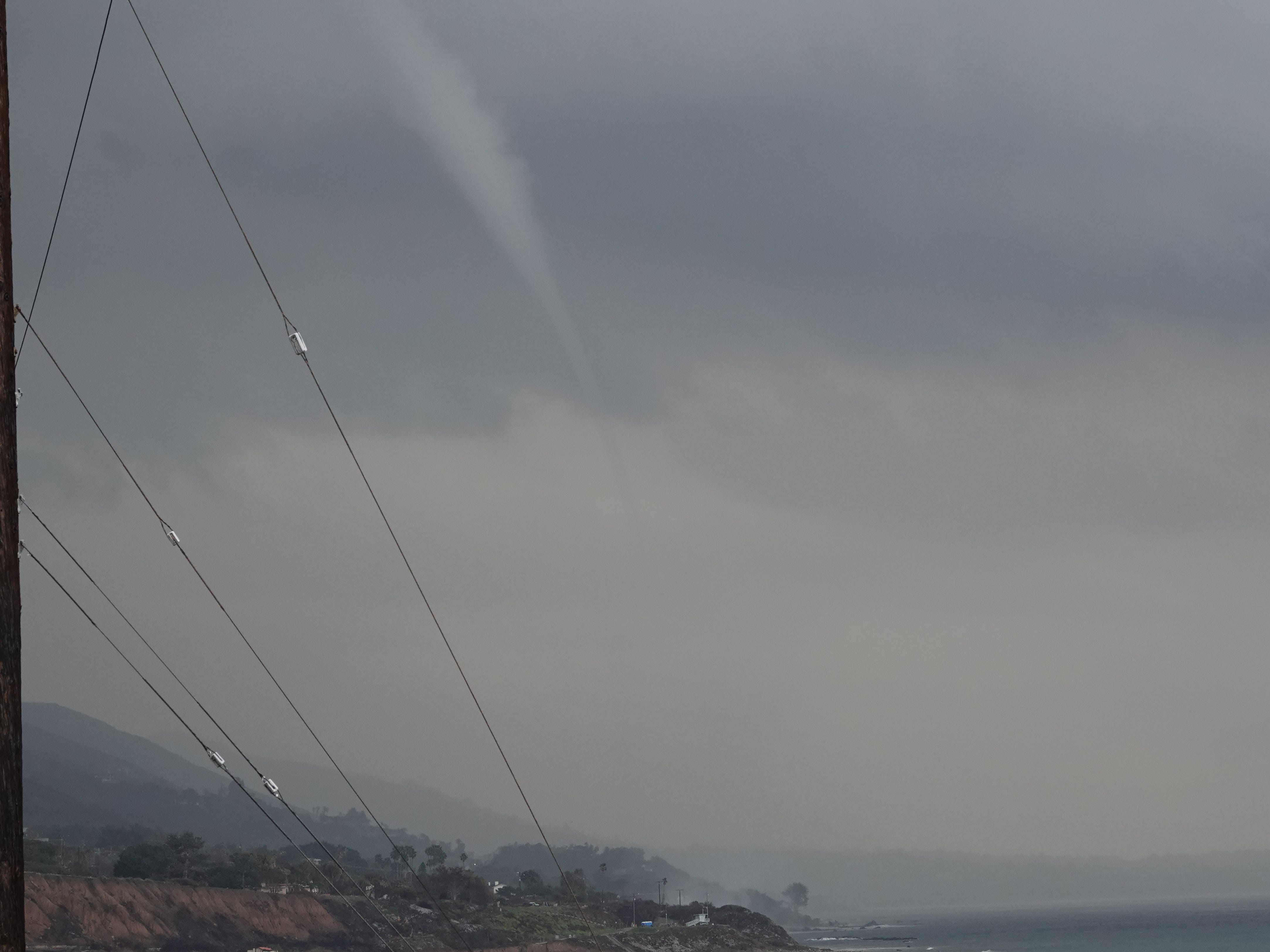 A funnel cloud moves toward shore off Pacific Coast Highway Saturday afternoon near the Ventura and Los Angeles county line as a storm system moved into the area.