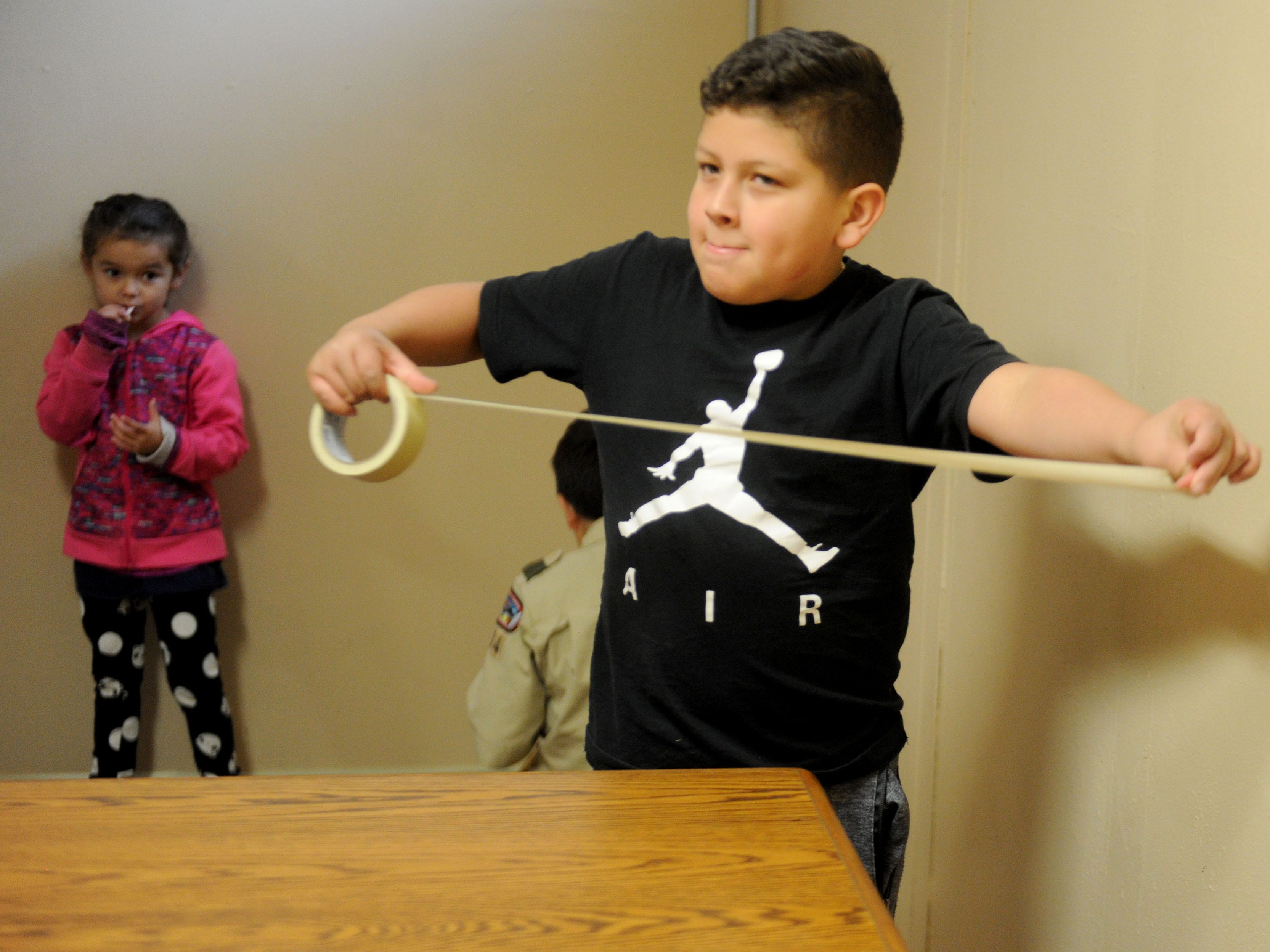Juan Barrera, 9, helps tape the edges before volunteers painted the walls at Oxnard National Guard Armory homeless shelter on K Street Saturday morning. The shelter opened on a temporary basis Saturday night because of the rain.
