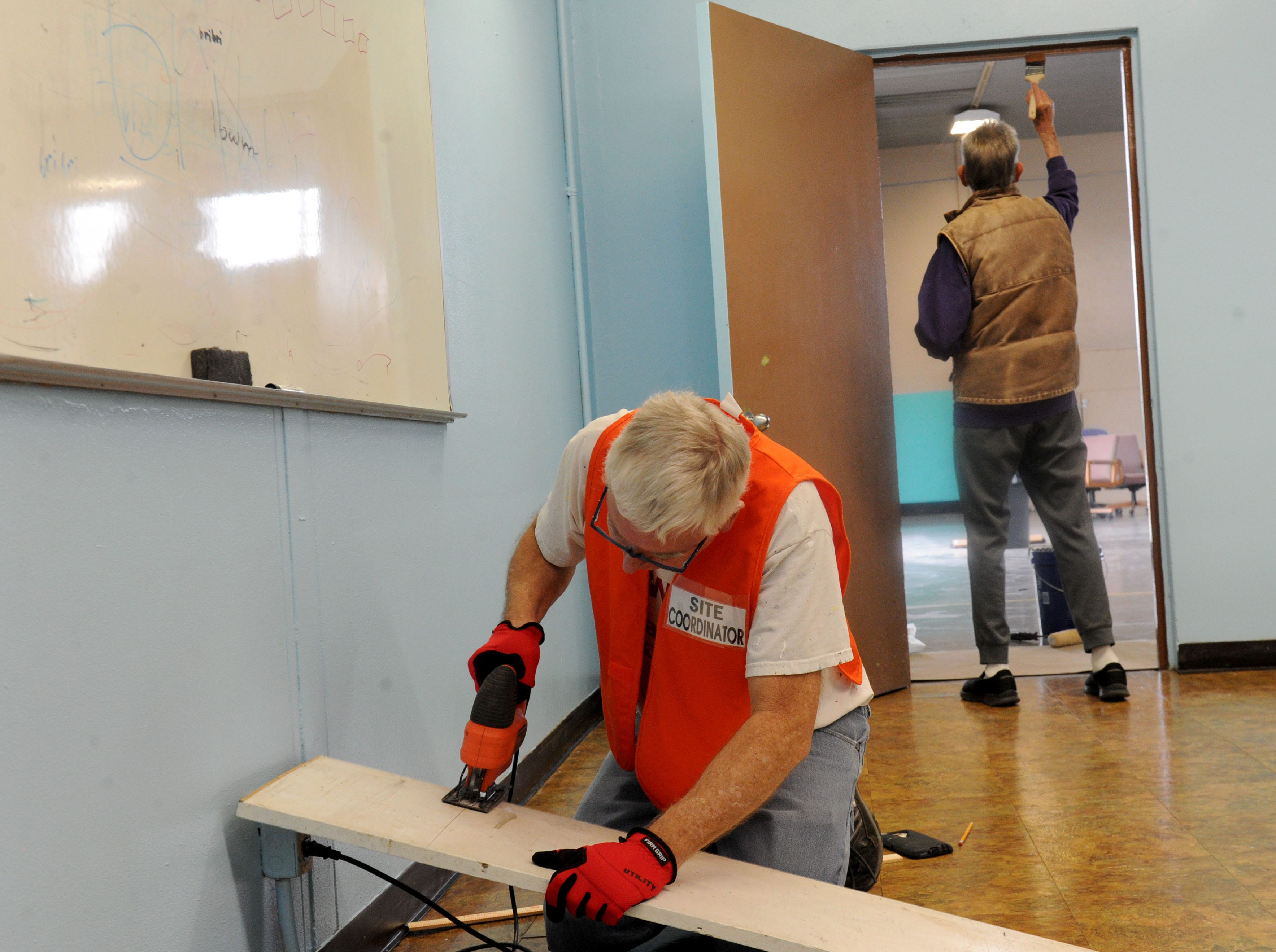 Karl Lawson, with the city of Oxnard's housing department, cuts a piece of wood to use on one of the beds at the homeless shelter as volunteers help get it ready to open. The 24-hour shelter is expected to open this month.