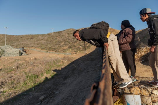 A migrant from Honduras looks from the border fence to the U.S. side before jumping to San Diego from Tijuana, Mexico, on Jan. 3, 2019.