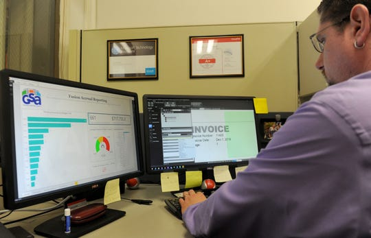 Jacob Ward, a record automation specialist for the Ventura County General Services Agency, goes through some invoices to send them to the correct departments. General Services designed a program to receive, scan and electronically route vendors' bills for approval and payment. Managers say its saves the county about $80,000 per year.