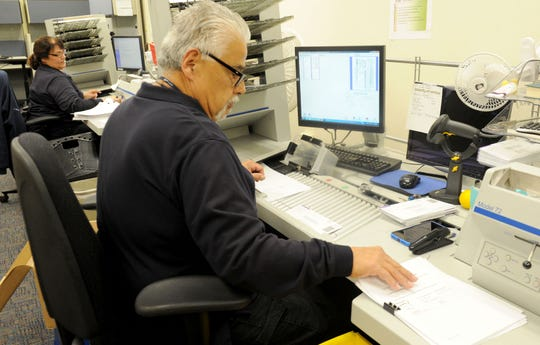 Edward Martinez, in the graphics department of the Ventura County General Services Agency, and Terry McLean (in the back) open and scan incoming mail. The General Services Agency has designed a program to receive, scan and electronically route bills that increases efficiency and saves money.