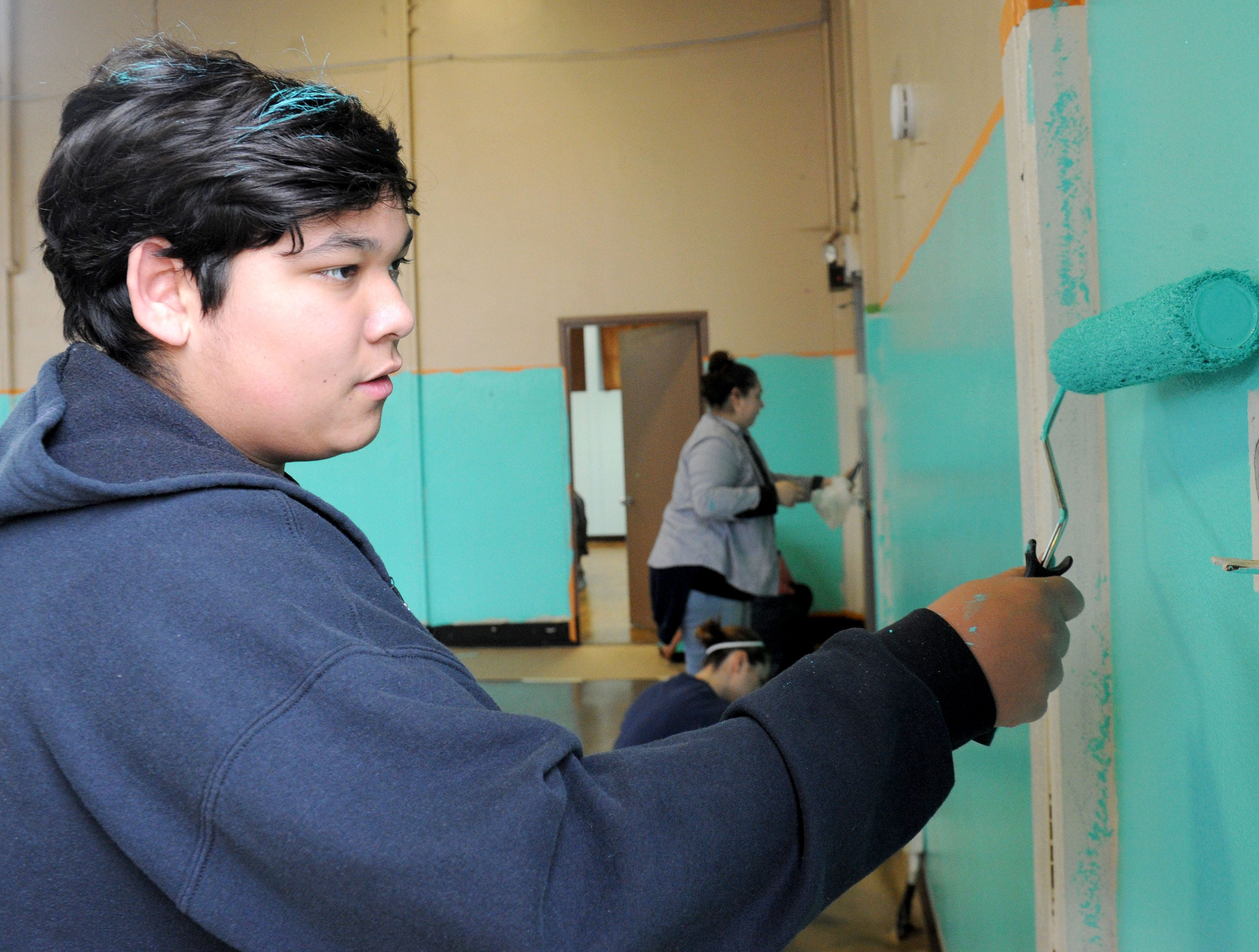 Isaiah Morales, 13, of Ventura helps paint the homeless shelter at the National Guard Armory in Oxnard Saturday morning.