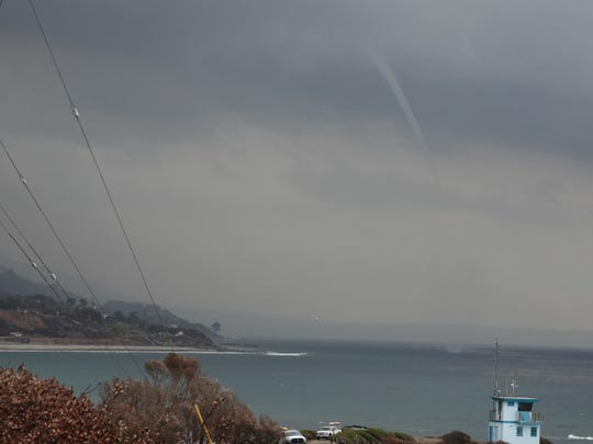 A funnel cloud kicks up ocean water off Pacific Coast Highway near the Ventura and Los Angeles county line Saturday afternoon.