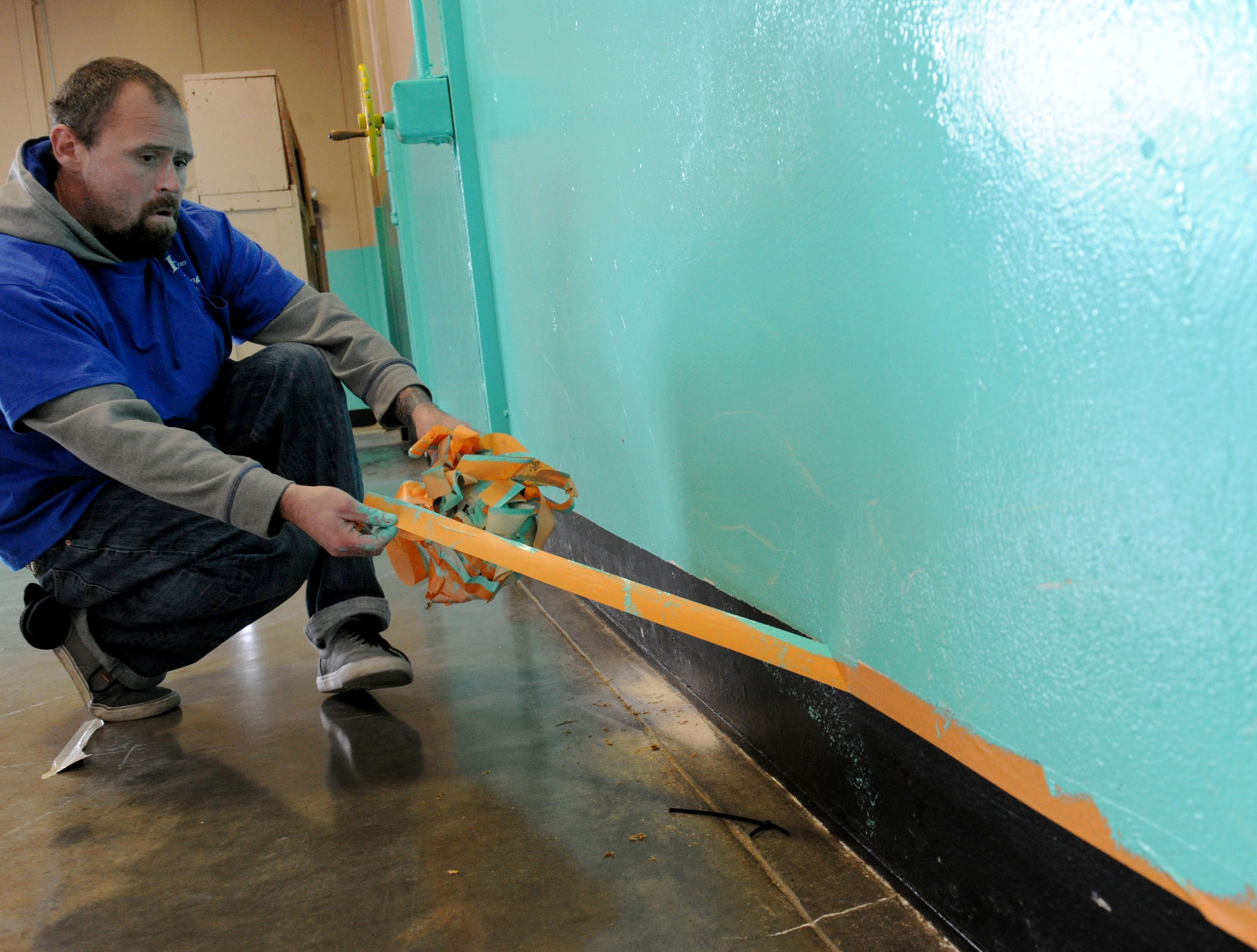 Jesse White of Oxnard, removes tape after volunteers painted the homeless shelter at the National Guard Armory in Oxnard Saturday morning.