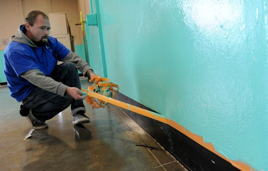Jesse White of Oxnard, removes tape after volunteers painted the homeless shelter at the National Guard Armory in Oxnard. By the end of the year, the city of Ventura plans to have a year-round homeless shelter up and running.