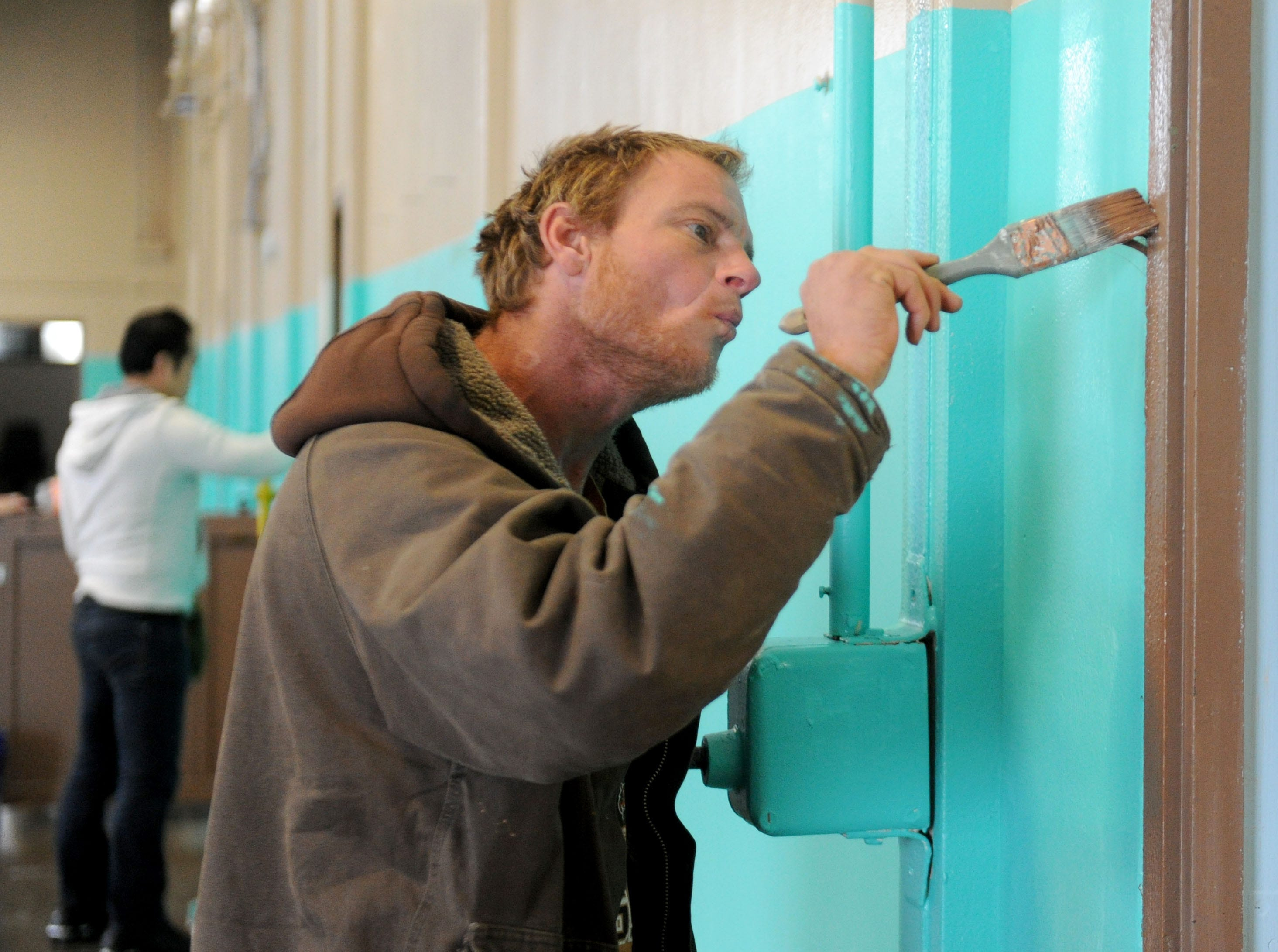 Aron Varney helps paint the homeless shelter in Oxnard Saturday morning. The 24-hour shelter at the National Guard Armory hasn't opened yet but the doors were opened temporarily Saturday night because of the rain.