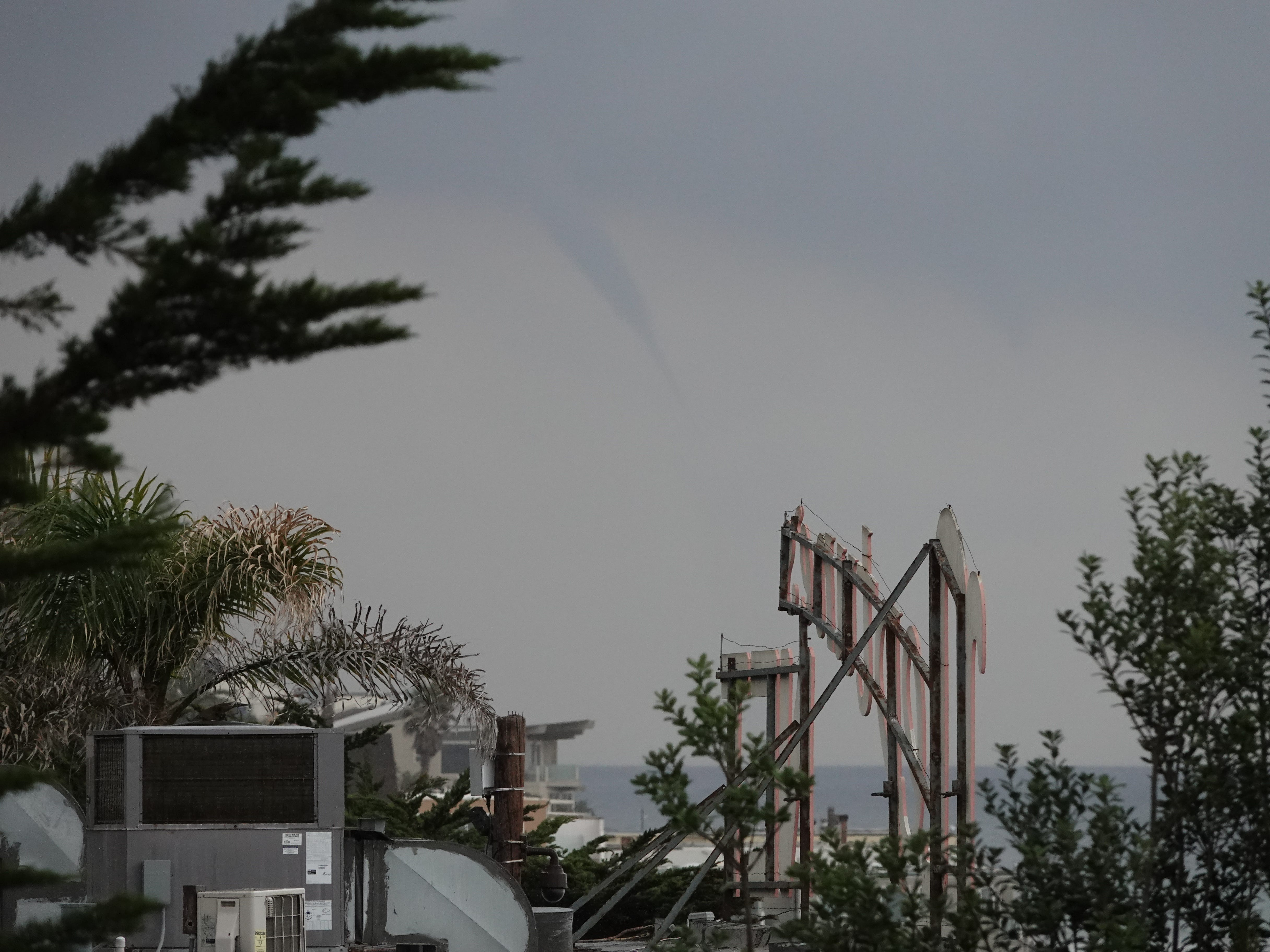 A funnel cloud seen from behind the Neptune's Net sign on Pacific Coast Highway Saturday afternoon as a storm system moved into the area.