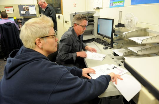 Graphic techs Tryna Ross (left) and Ryan Hill (right), scan invoices for the Ventura County General Services Agency.