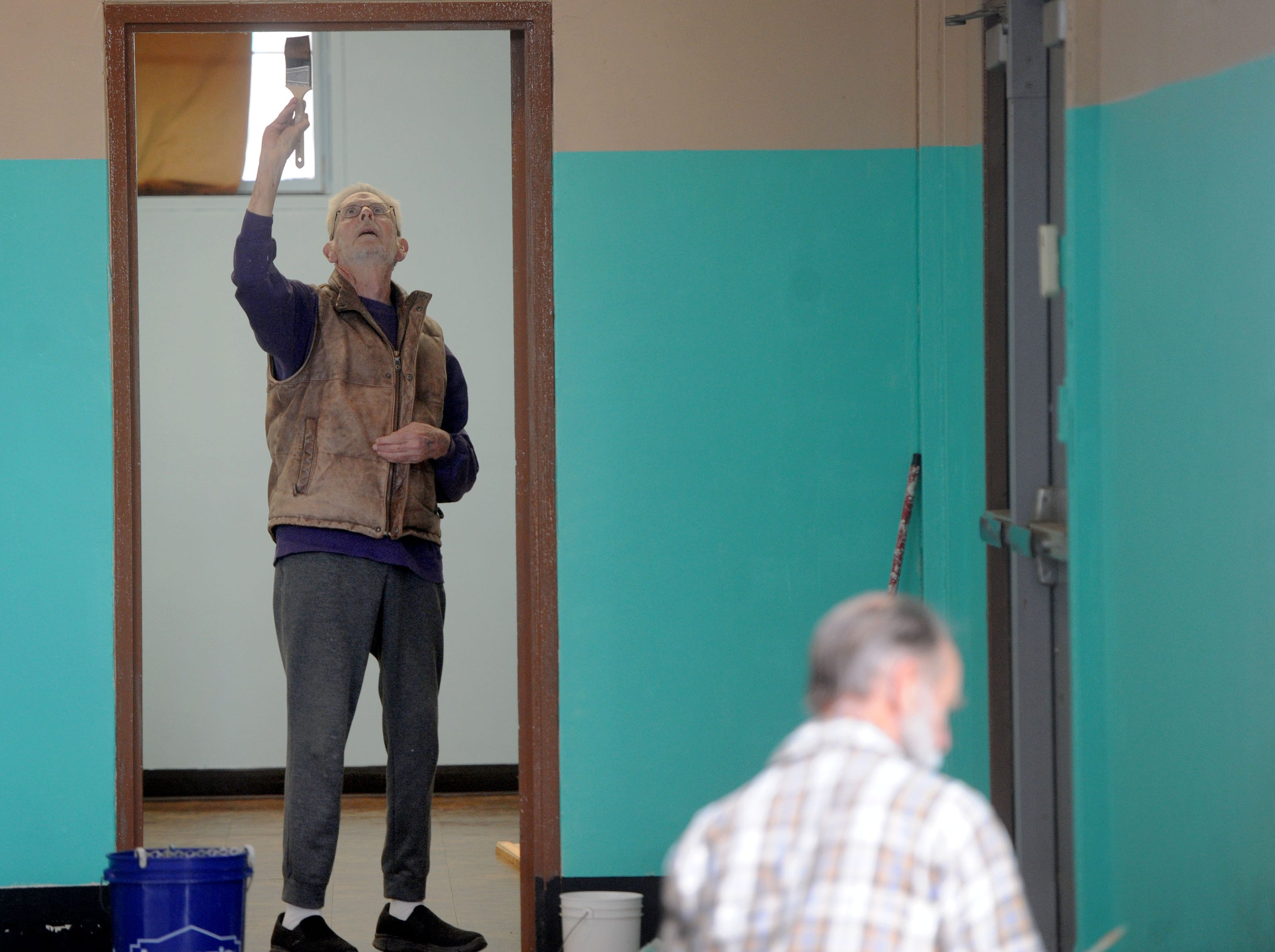 Harold Cartlidge, of Ventura, helps clean up the edges to the door frame as volunteers painted and cleaned the homeless shelter at the National Guard Armory in Oxnard Saturday morning. The shelter opened temporarily Saturday night because of the rain.