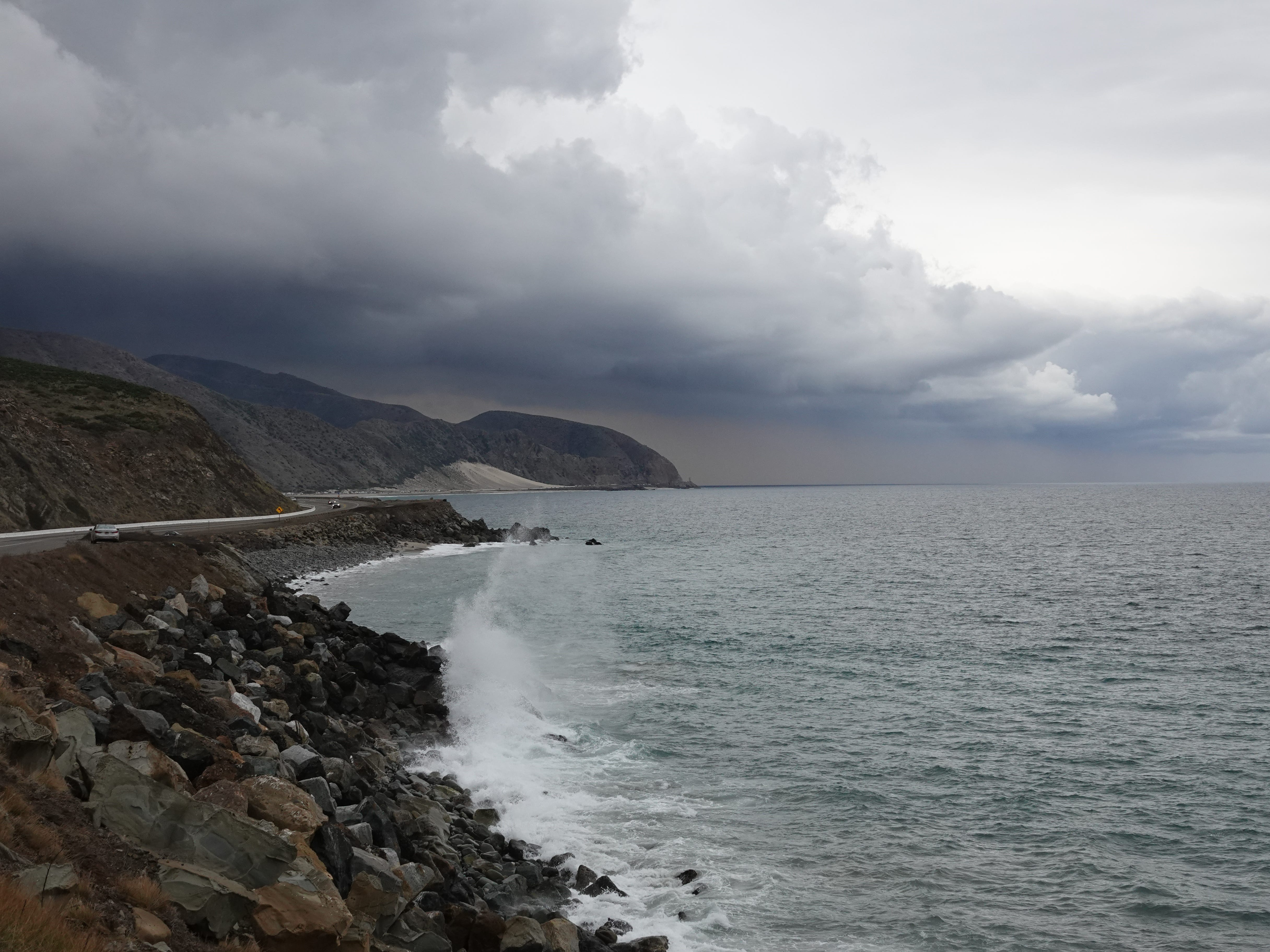 Storm clouds loom over Pacific Coast Highway as a wave breaks on rocks south of Mugu Rock Saturday.