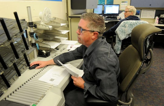 Ryan Hill, a graphic tech for the General Services Agency of the county of Ventura, scans invoices. The agency designed a program that creates efficiencies and saves the county money.