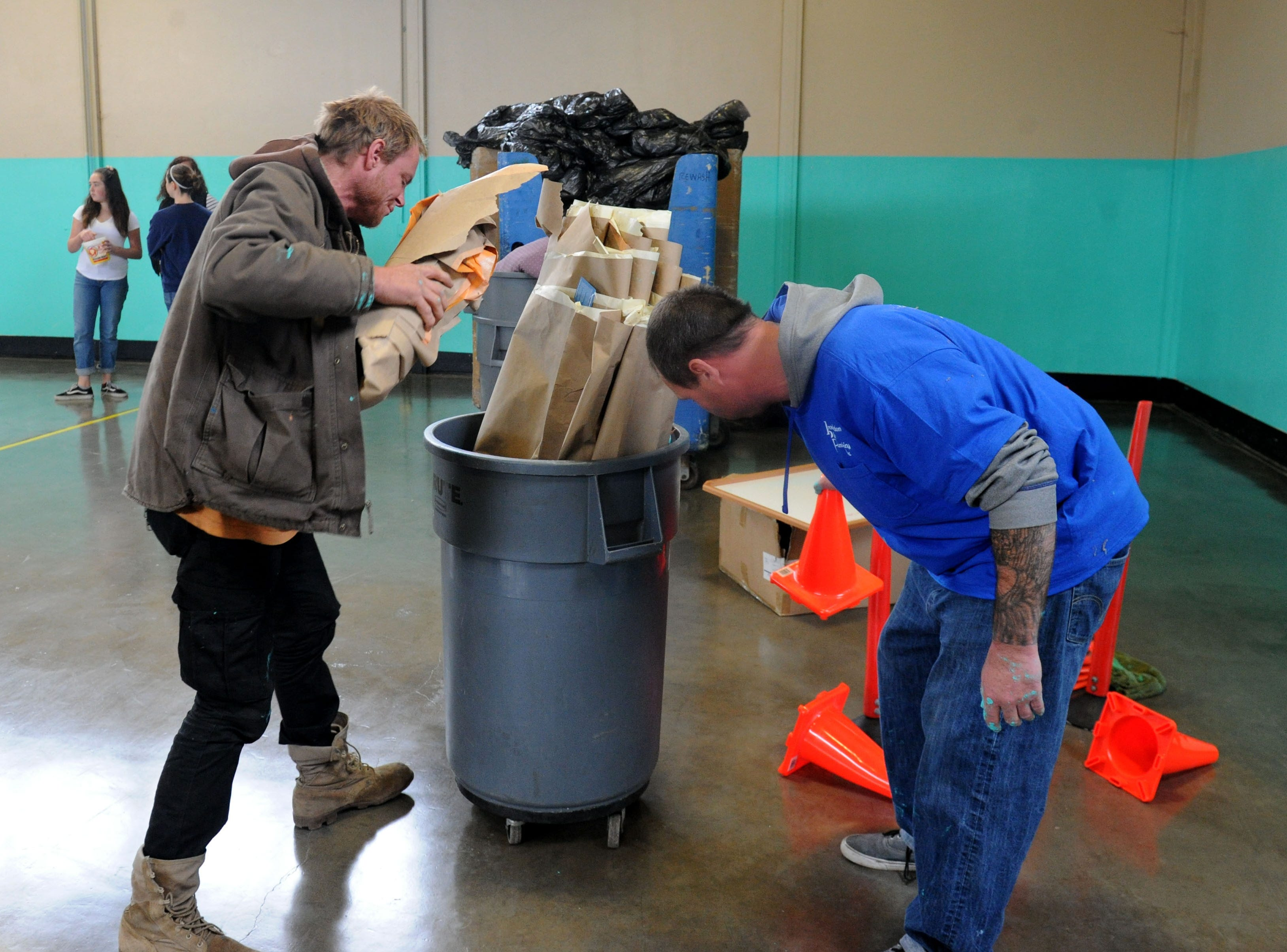 Volunteers Aron Varney (left) and Jesse White help clean up the homeless shelter Saturday at the National Guard Armory in Oxnard. Volunteers painted and cleaned so it could temporarily Saturday night because of the rain.