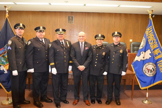 The four newly promoted Harrison police officers stand with Mayor Ron Belmont, center right, and Chief Joseph Yashinski, center left. Sgt. Richard Abbate is pictured second from right.