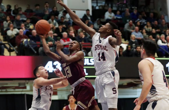 Iona's Ronald Greene Jr. (13) drives to the basket in front of Stepinac's Ed Sanchez (3)   during the Crusader Classic at the Westchester County Center in White Plains Jan. 4, 2019. Iona won the game 60-55.