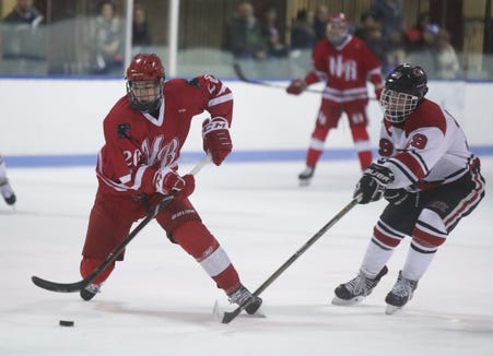 North Rockland's Luke Morris (20) works the puck past Rye's Graham Ross (19) during ice hockey action at Playland Ice Casino in Rye on Friday, January 4, 2019.