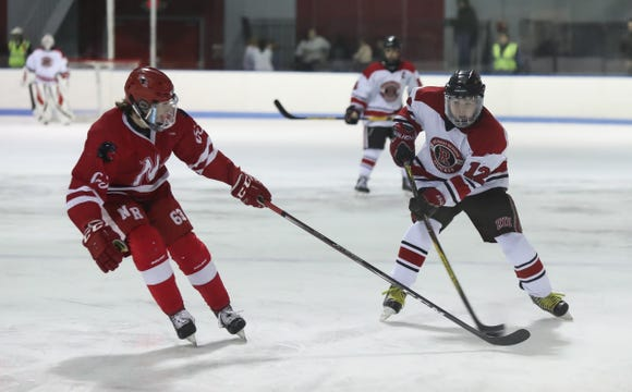 North Rockland's Alex Bailek (63) works to knock the puck away from Rye's Connor O'Brien (12) during the first period ice hockey action at Playland Ice Casino in Rye on Friday, January 4, 2019.