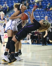 Delaware's Makeda Nicholas (left) is fouled by James Madison's Lexie Barrier in the first half of the Hens' opening game in CAA play at the Bob Carpenter Center Friday.