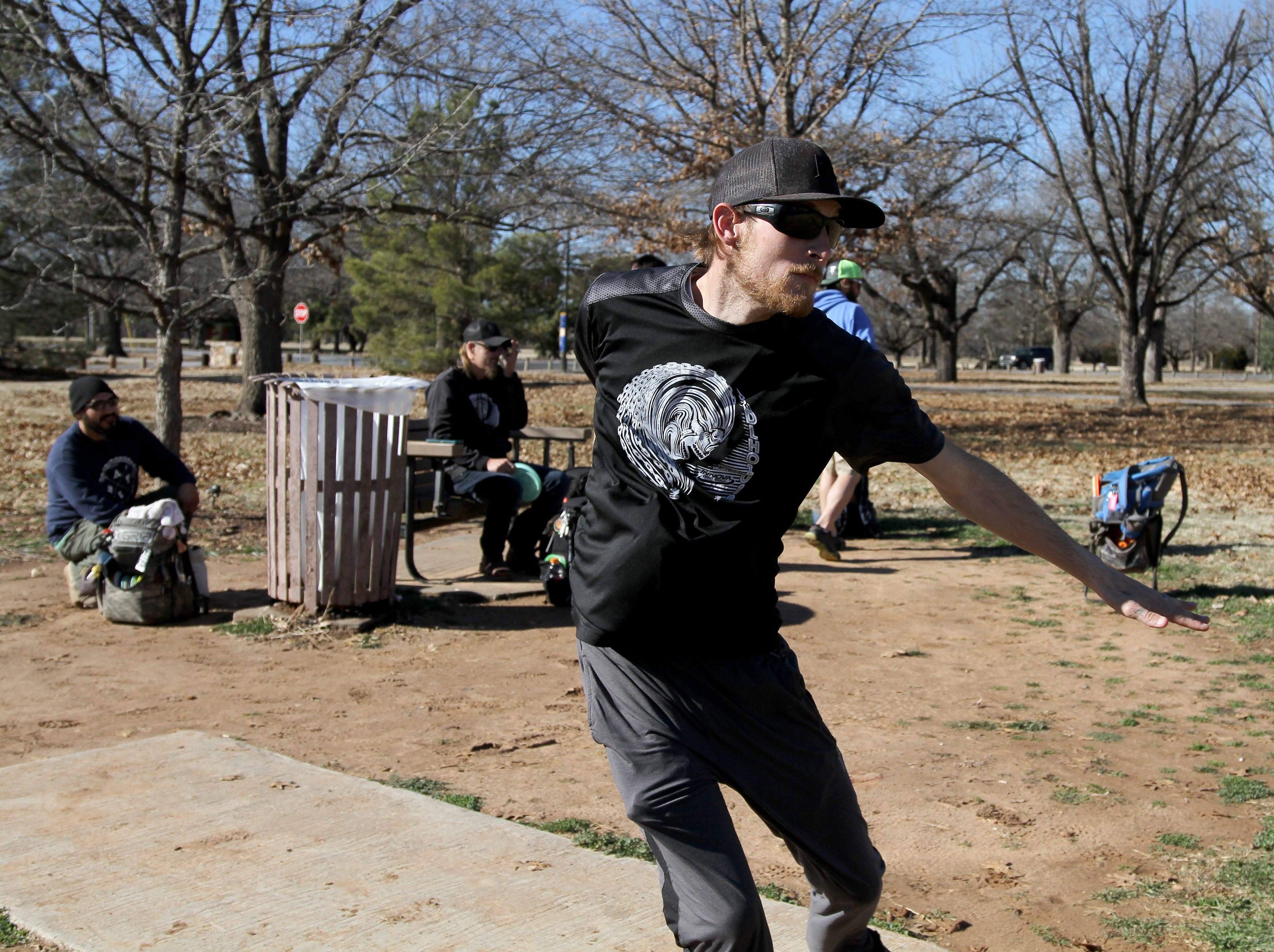 JD Cmompton watches his throw while playing disc golf with friends Saturday, Jan. 5, 2019, in Lucy Park.