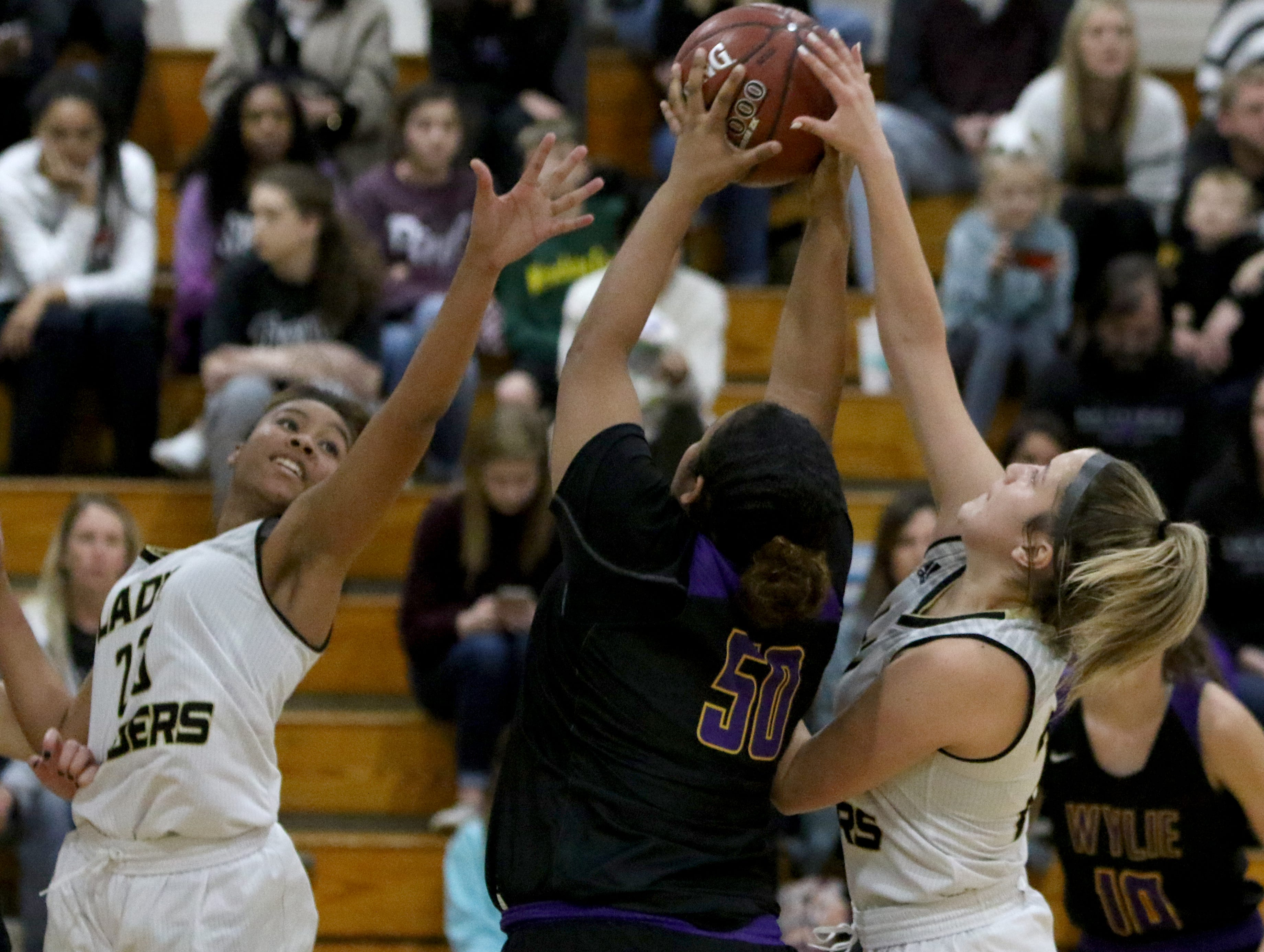 Rider's Taleyah Jones, left, Atlea Cooke and Abilene Wylie's Kalilah Modest (50) go for the rebound Friday, Jan. 4, 2019 at McNiel Middle School.