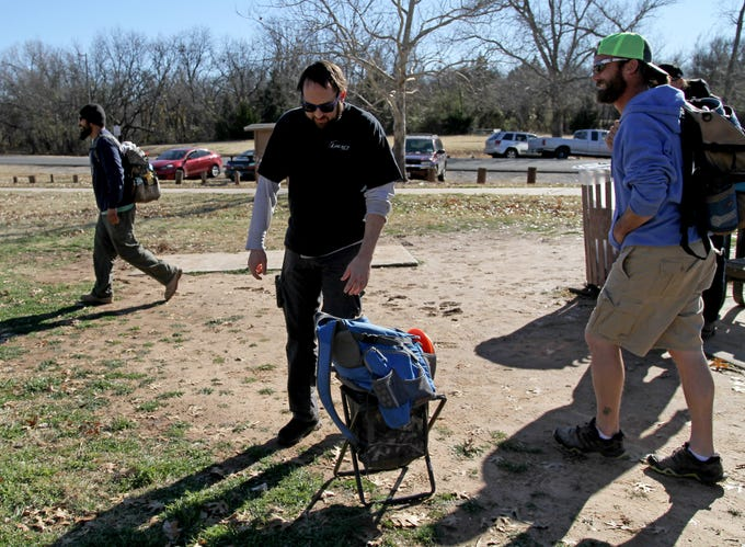 Eric Davis picks up his pack to head to where his disc landed while playing disc golf Saturday, Jan. 5, 2019, in Lucy Park.