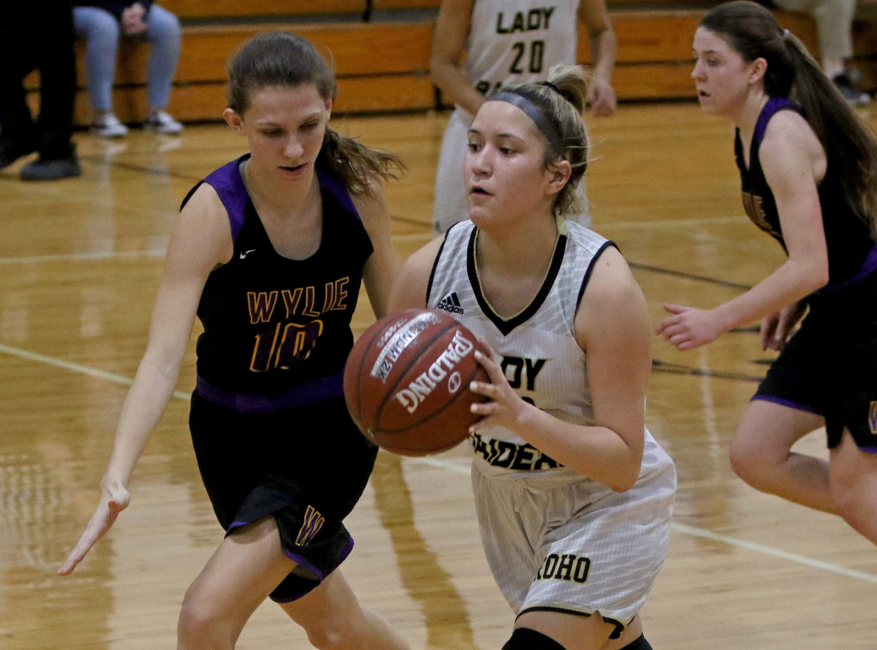 Rider's Atlea Cooke passes by Abilene Wylie's Abbey Henson Friday, Jan. 4, 2019 at McNiel Middle School.