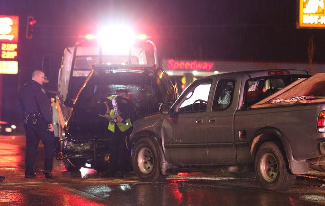 Zanesville Police Department officers look at a truck that hit a Muskingum County Sheriff's Office cruiser Friday night.