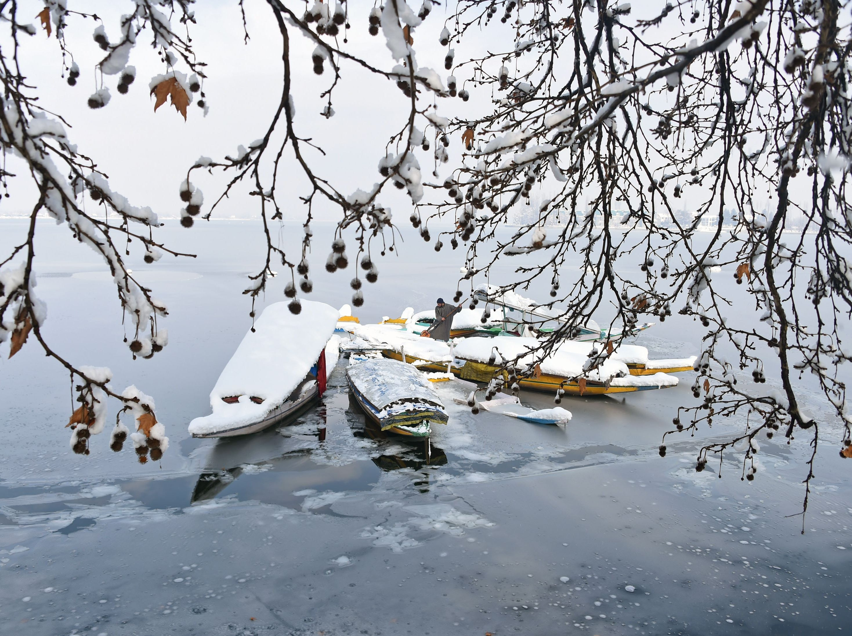 A Kashmiri boatman clears snow from Shikara boats near a frozen portion of Dal Lake after a snowfall in Srinagar on Jan. 5, 2019. Kashmir's road links with the rest of India were cut off as heavy snowfall closed the Jammu-Srinagar national highway.