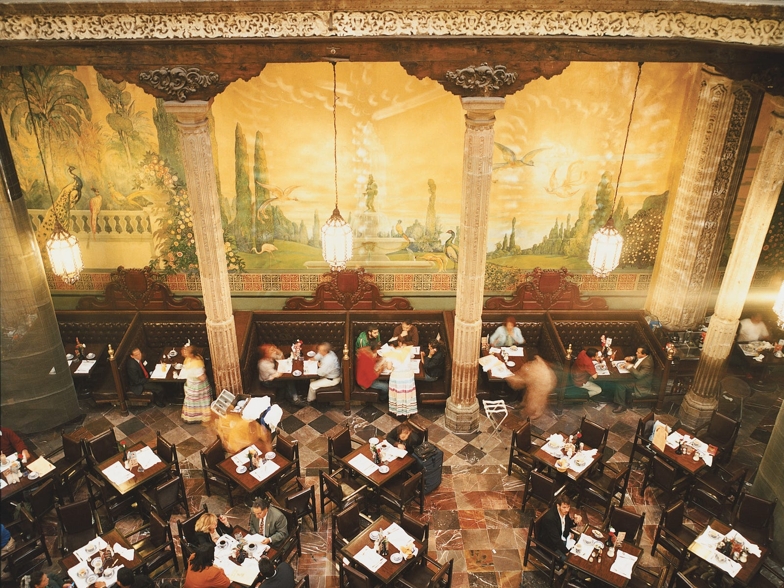 The interior of Sanborns Casa de los Azulejos restaurant features floor-to-ceiling murals in the courtyard of the historic palace.