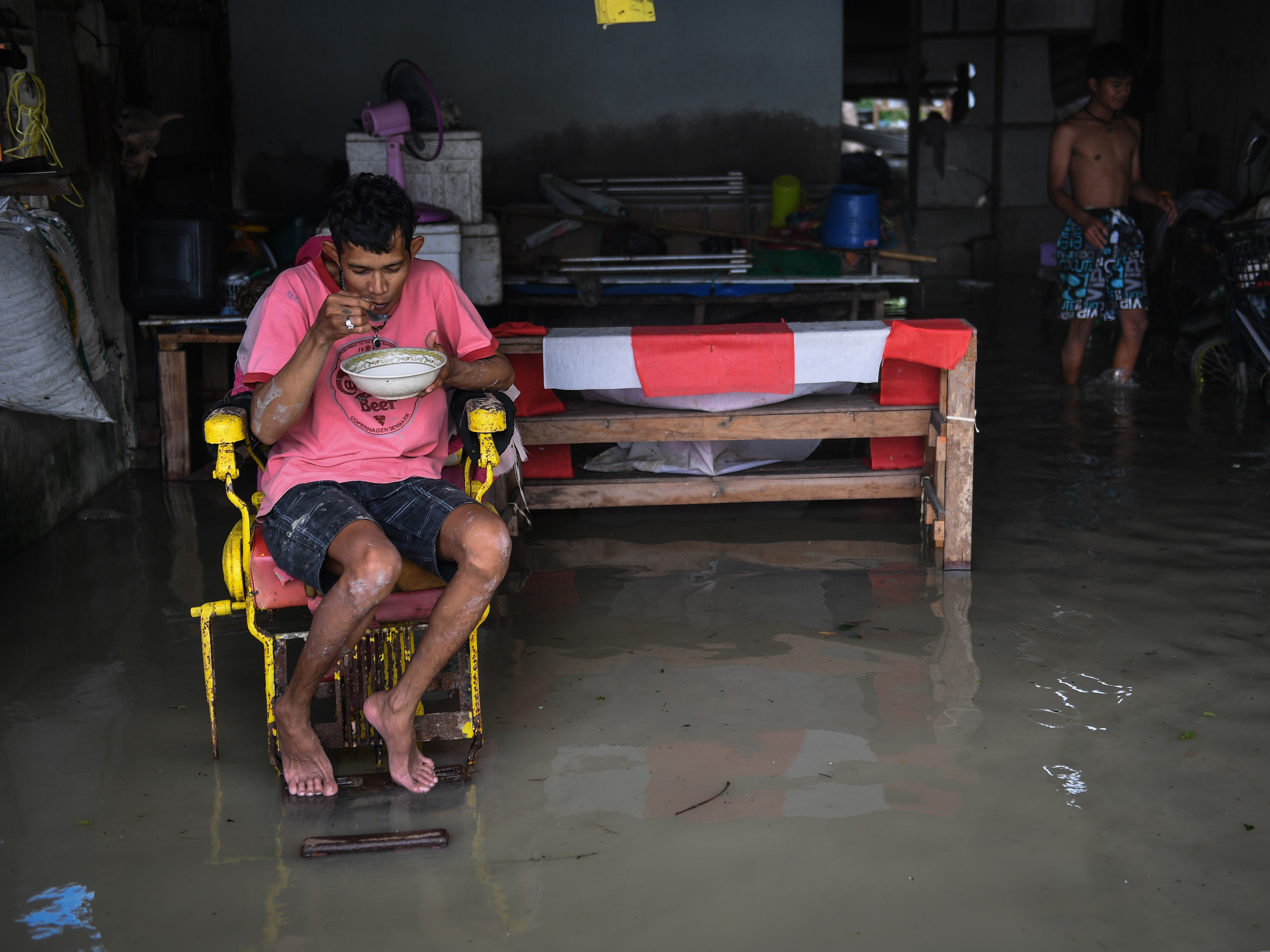 A man eats in his flooded home in the aftermath of tropical storm Pabuk in the southern Thai province of Nakhon Si Thammarat on Jan. 5, 2019.