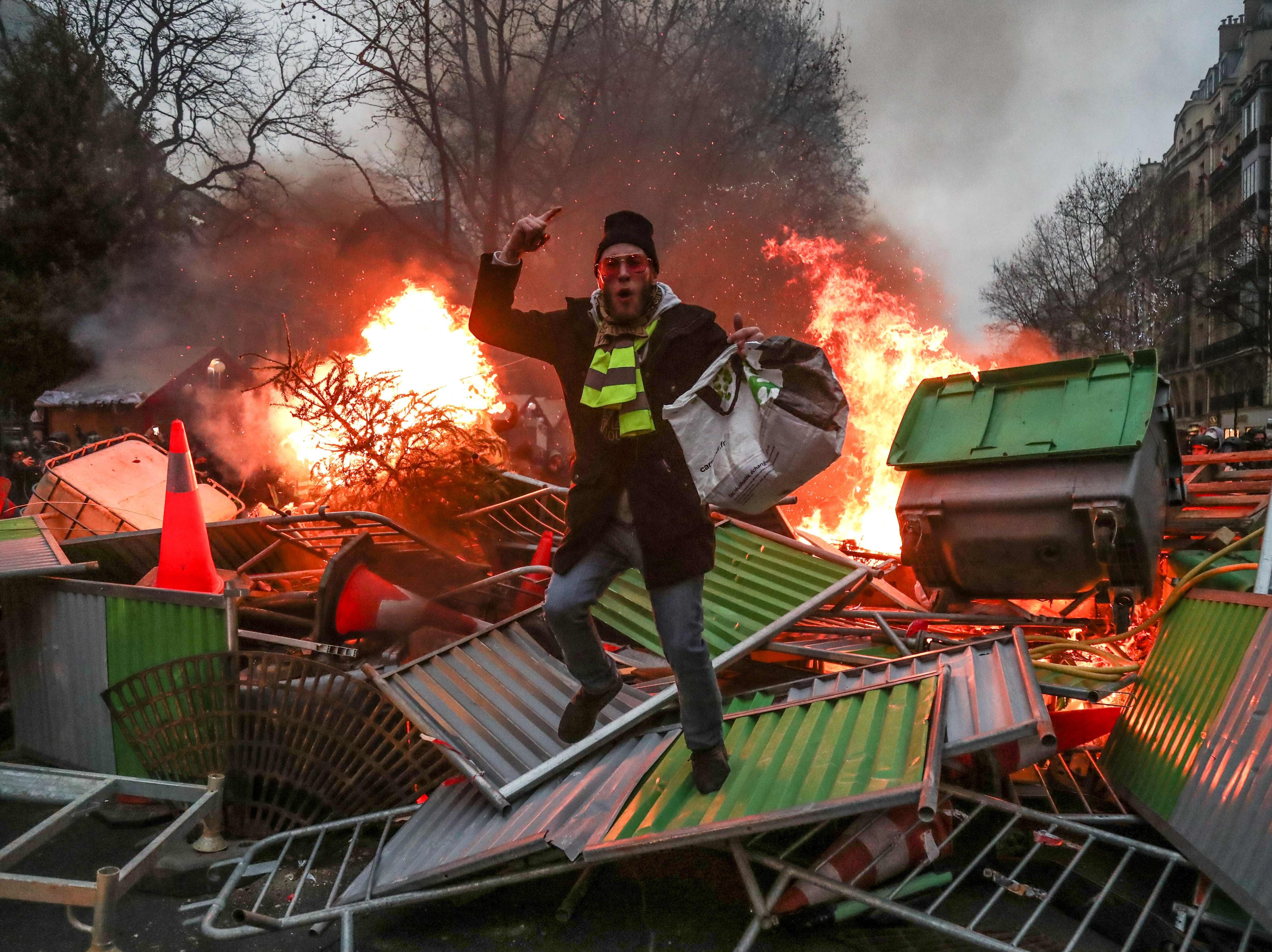 "A yellow vest ""Gilets Jaunes"" anti-government protestor stands on a burning barricade in Paris on Jan. 5, 2019 during clashes with security personnel."
