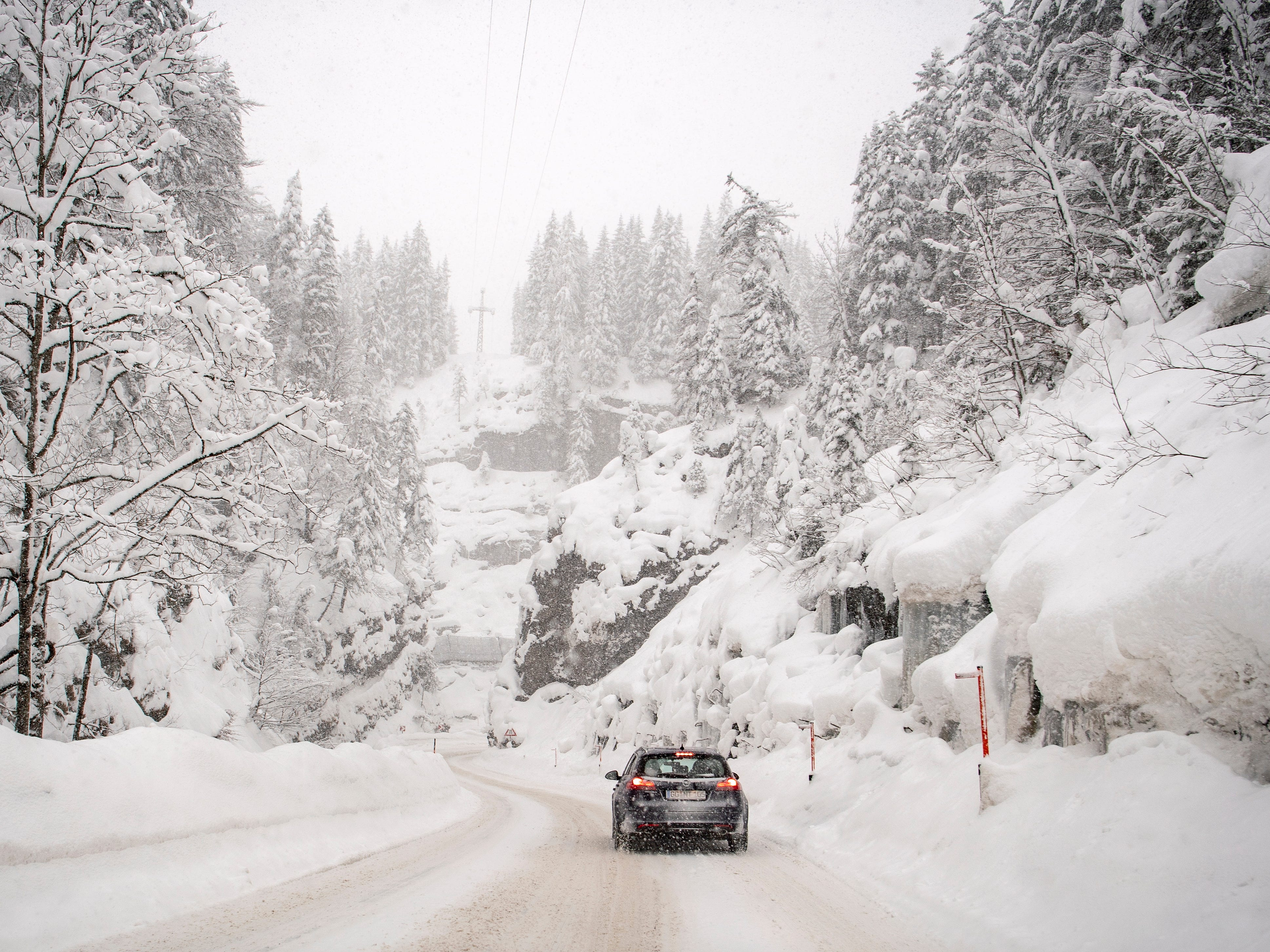 A car drives through a snow covered road during heavy snowfall near Obertauern, Austria on Jan. 5, 2019. Austria and southern Germany are expected to receive heavy snowfalls over the weekend. Weather forecasts warn that the snowstorm could cause roadblocks and increased avalanche danger in many parts of the affected region.